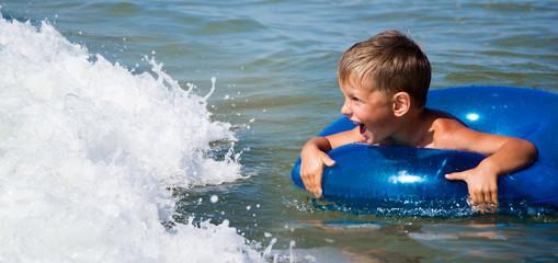 boy in a swim ring against waves