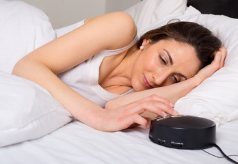 young woman turning off the alarm clock in the morning