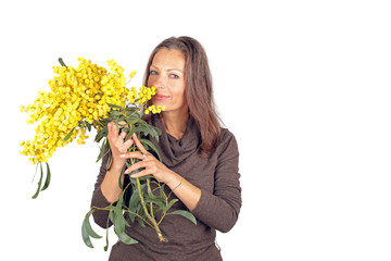 Beautiful woman with blossoming mimosa