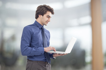 Portrait of young businessman holding laptop