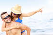 Young couple pointing at something at the beach