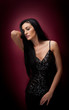 Attractive brunette woman in a black posing dramatic on purple