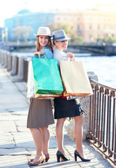 Two beautiful girls with shopping bags in the city