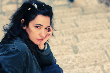 Portrait of sad 35 years old woman sitting in the street
