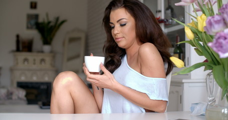 Gorgeous young woman sitting drinking coffee