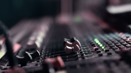 Audio Engineer adjusting faders on his mixing console desk