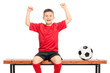 Joyful junior player in red shirt gesturing happiness seated on
