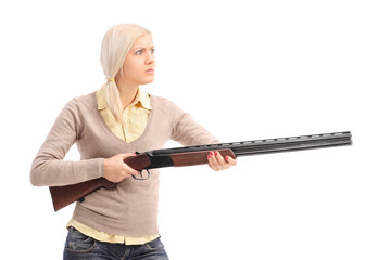 Furious young blond woman holding a shotgun ready to shoot