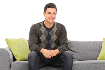 Cheerful handsome young man sitting on a modern sofa