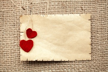 Paper. Two red plastic hearts and carton card on a canvas