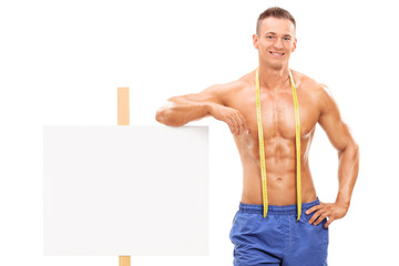 Handsome, naked young man standing by a banner