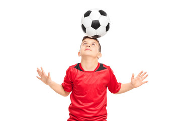 Junior soccer player wearing red shirt joggling with a soccerbal