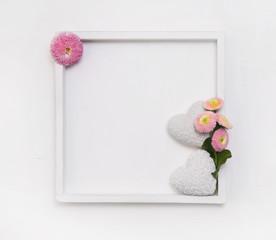 Weißer Holzhintergrund mit Gänseblümchen und zwei Herzen
