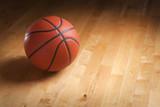 Basketball on hardwood court floor with spot lighting