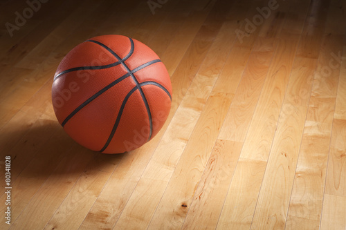 Basketball on hardwood court floor with spot lighting - 80341828