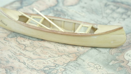 A small wooden boat on top of the map