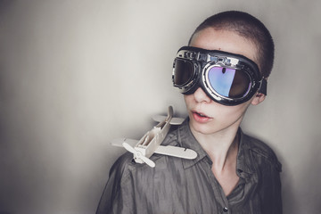 girl in retro pilot glasses with wooden plane