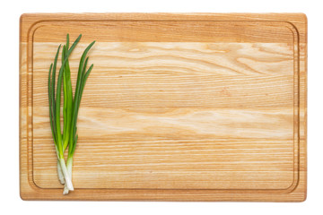 Fresh green onion on wooden board. Isolated on white background