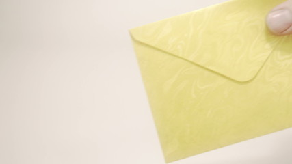 A yellow envelope is handed to the lady