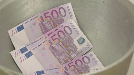 Four 500 Euro bills inside a pale