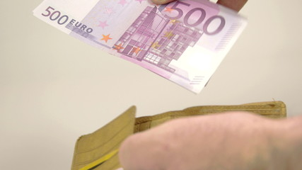 A man gets 500 Euro bills from his wallet