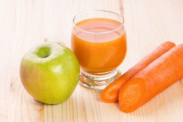 Glass of fresh apple carrot juice on wooden background