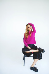 Trendy woman model with chair in pink on isolated background