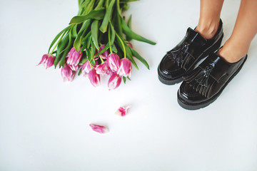 Fine trendy black leather brogues on women legs with flowers