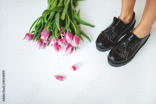 Fine trendy black leather brogues on women legs with flowers - 80348419