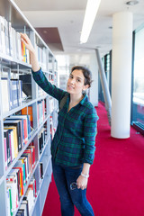 Young Student Searching for a Book at Library