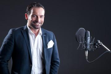 Junger Mann steht vor Mikrofon im Studio und lächelt