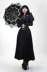 Gothic vampire in black dress with umbrella