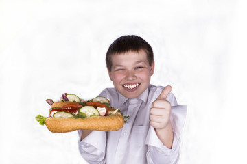a boy of twelve years holding two hot hot dog