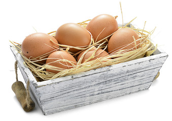 Organic eggs in wooden box isolated on white background.