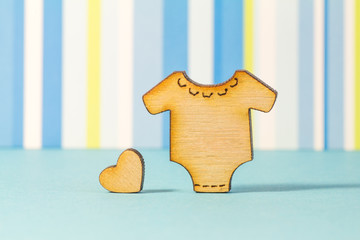 Wooden icon of baby bodysuit with little heart on blue striped b