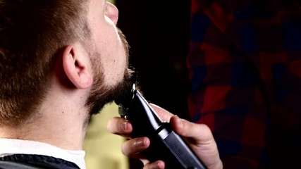 Master barber shop haircut beard makes the client using machines
