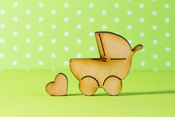 Wooden icon of baby carriage and little heart on green backgroun
