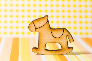 Wooden icon of children's rocking horse on yellow background