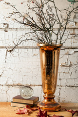 Copper vase with twigs against distressed wall. Grunge style