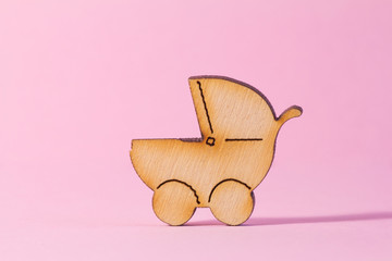 Wooden icon of baby carriage on pink background
