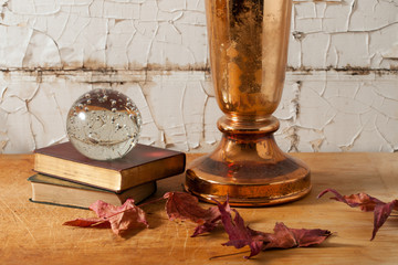 Copper vase and glass ball against distressed wall
