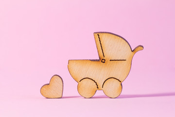 Wooden icon of baby carriage and little heart on pink background