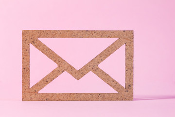 Wooden envelope icon on pink background