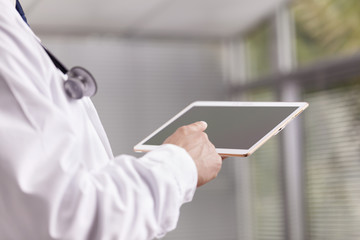 Close-up of a doctor working with a digital tablet