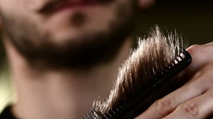 Male hand cut their hair. Lifted her hair and starts work with