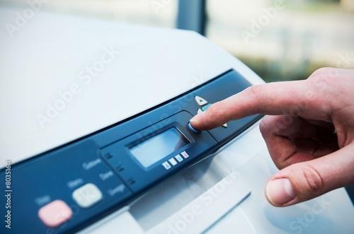 Finger on start button of laser printer - 80351611