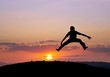 silhouetted boy jumping in sunset