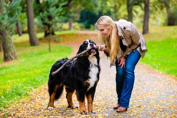 Frau und Hund beim Apportieren von Stock