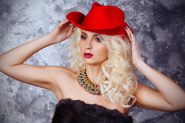 Portrait of a beautiful, sexy girl in a red cowboy hat