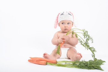 Baby boy in rabbit hat holding fresh carrot looking with distrus